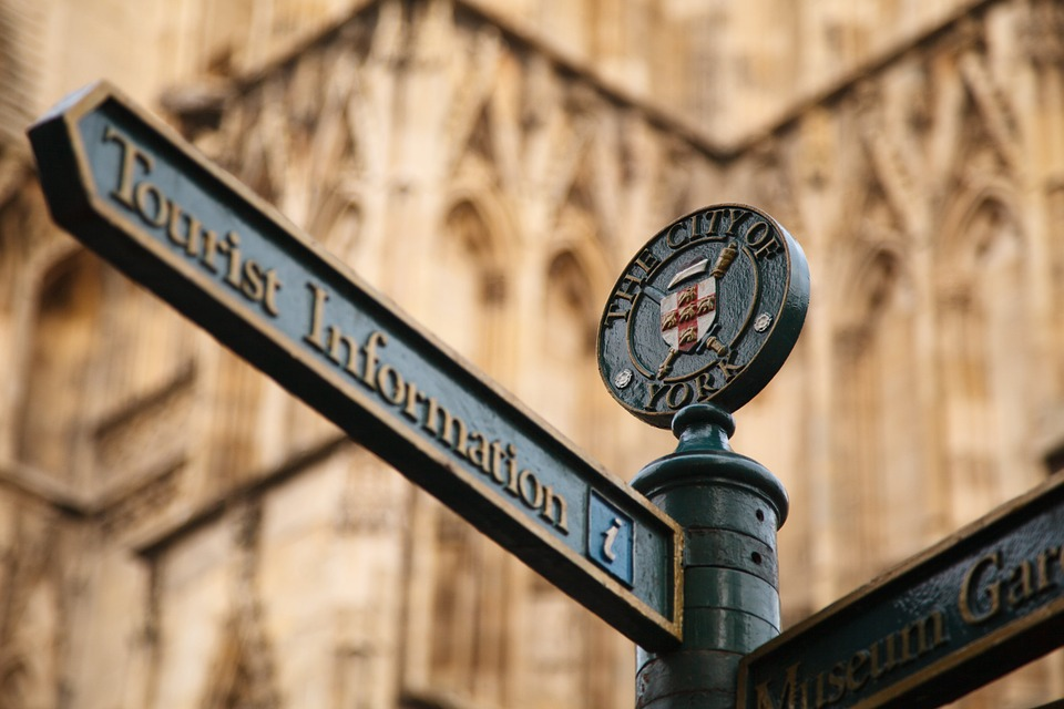 A sign metal sign post in front of a church in York, England pointing to Tourist Information.