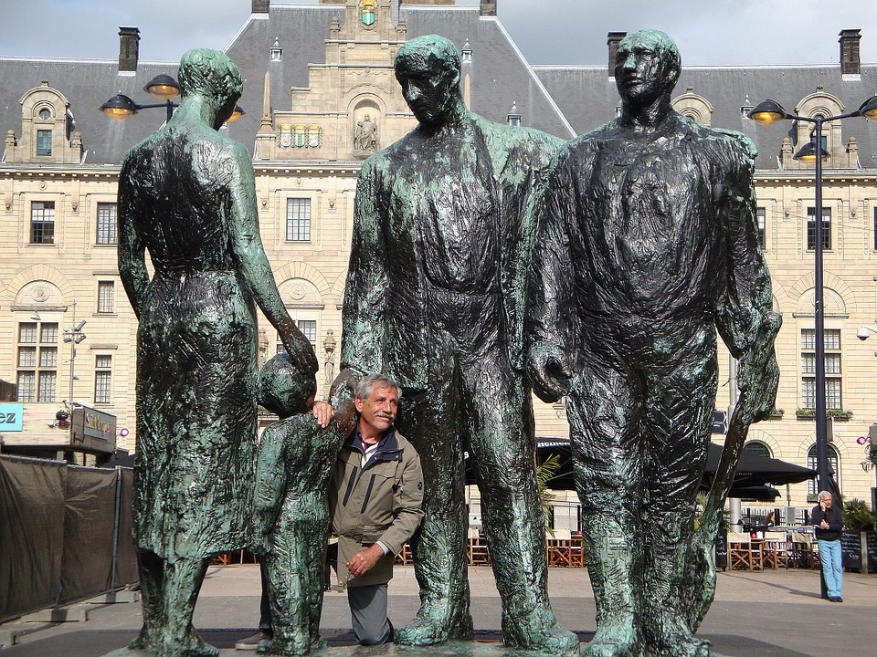 A man poses on one knee in the middle of a metal statue of two men, a woman, and a child.