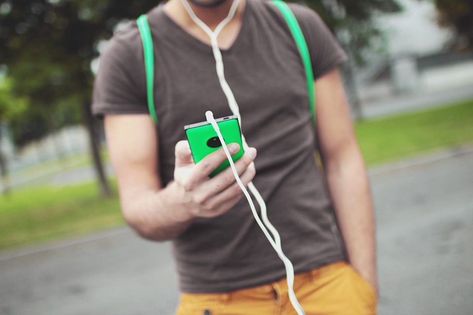 The burred torso of a man with headphones on holding his in-focus phone in front of him.