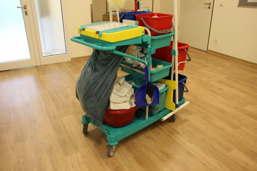 A hotel cleaning trolley in a hallway with wood floors.