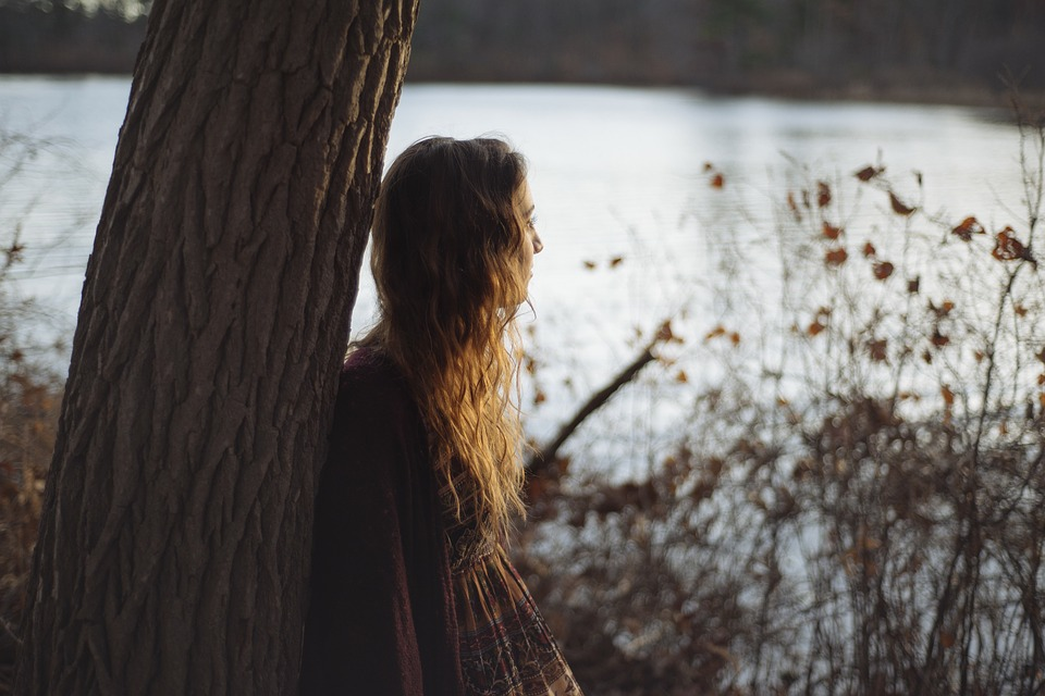 A young woman leaning against a tree staring out at a pond.