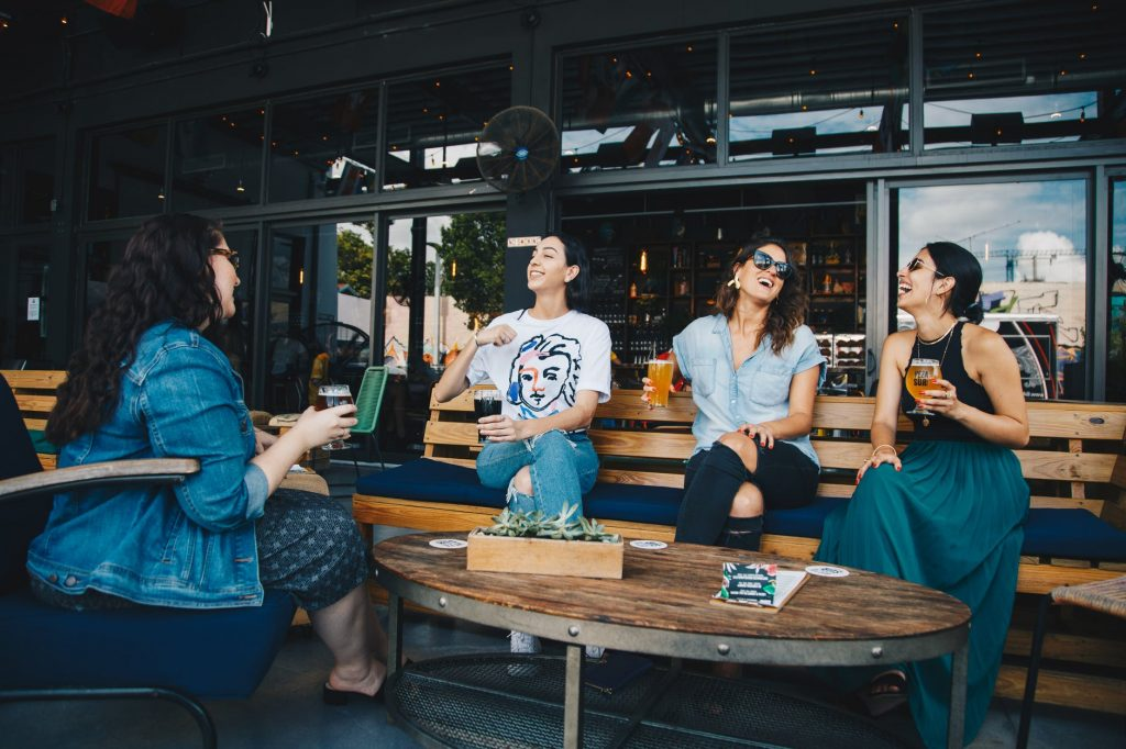 Four young women sitting outside a bar laughing and drinking beers.