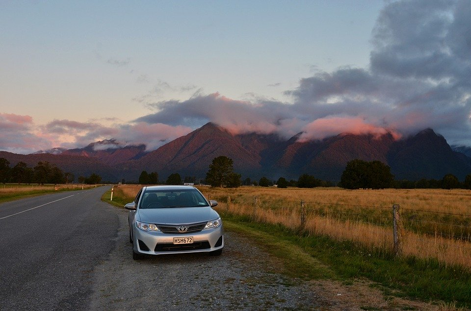 New Zealand mountains at sunset with a road and field in the foreground. A silver car is pulled off the road in a turnoff.