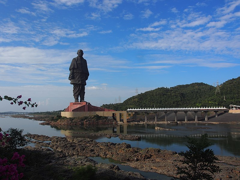 The Statue of Unity in the distance stands on top of a building with a bridge leading in from the right side. A blue sky and some hills lie behind the statue with a river and some rocks in front of it.