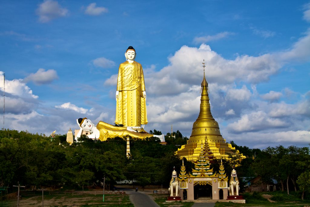 A distance photo of the yellow and white Laykyun Sekkya statue of Buddha and the second reclining Buddha at its feet. Trees and a golden-roofed temple in the foreground.