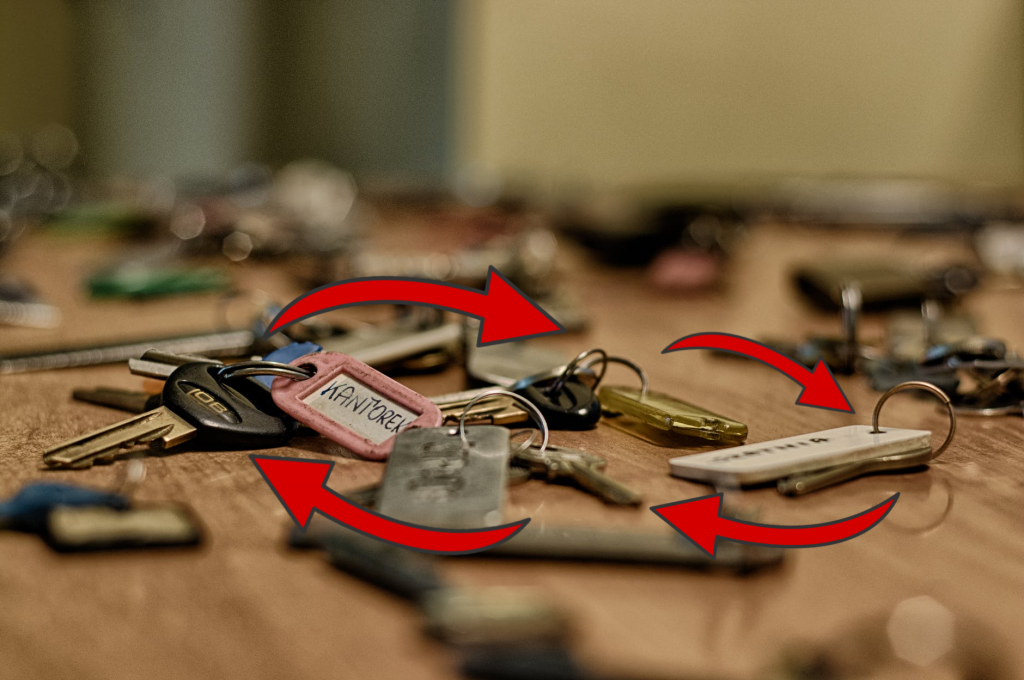 Dozens of sets of keys on a table with red arrows connecting them.