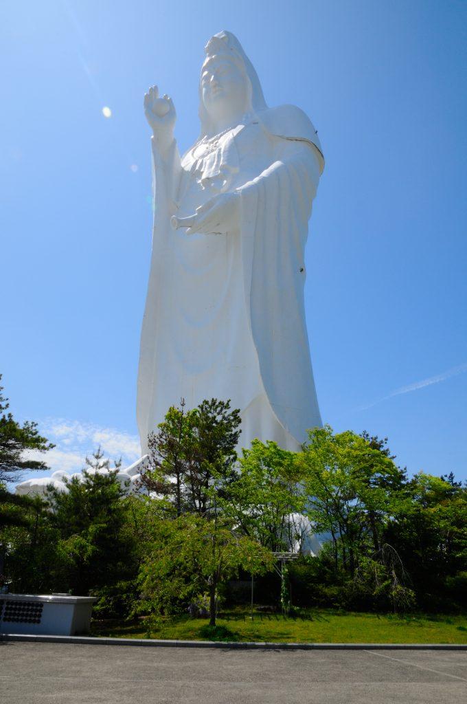Looking up at the tall, white Sendai Daikannon statue. Blue sky behind and trees at its feet.