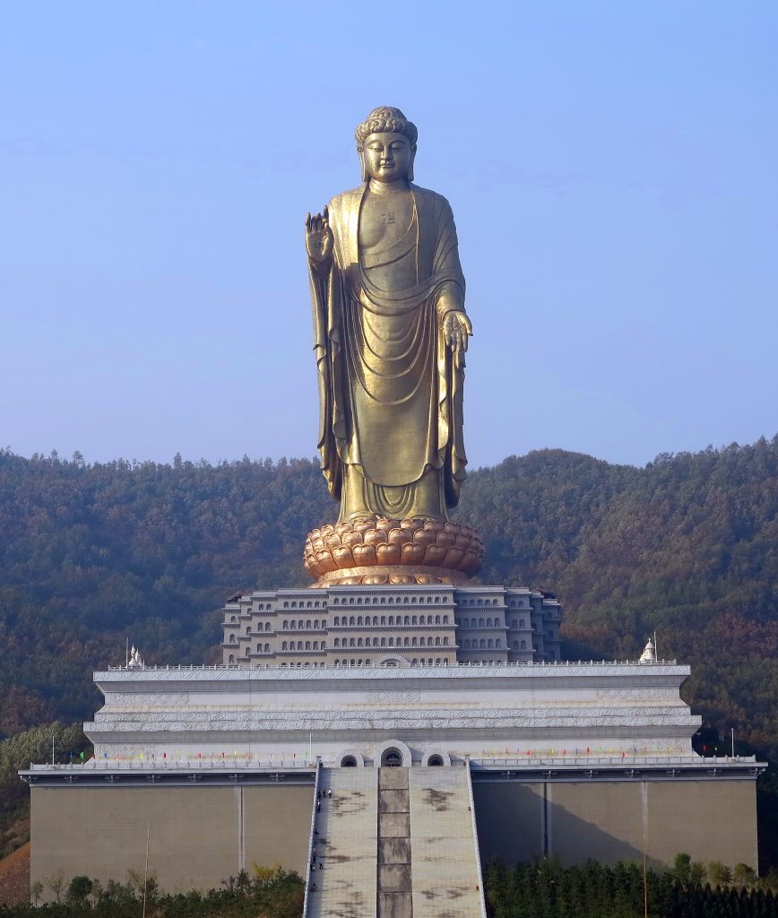 The Spring Temple Buddha statue against a clear blue sky. Including the temple building it stands on and the stairs leading up to the temple.