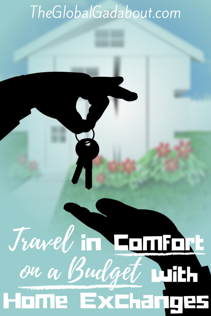 "The graphic of a house & yard out of focus in the background. Black silhouettes of a hand dropping keys into another hand in the foreground. White words read ""TheGlobalGadabout.com"" across the top and ""Travel in Comfort on a Budget with Home Exchanges"" across the bottom."