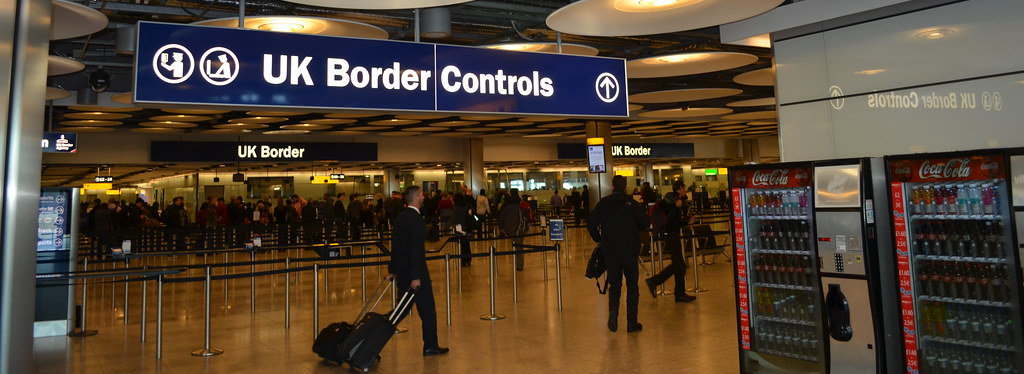 "Lines of travelers at airport customs under a sign reading ""UK Border Controls"""