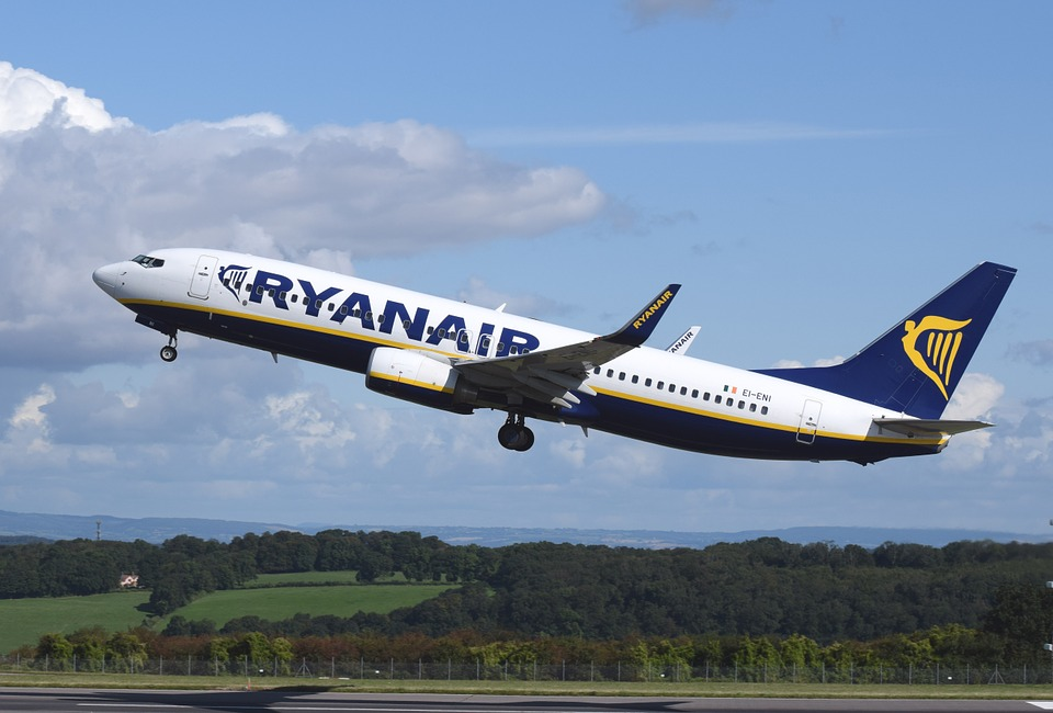 A RyanAir plane taking off with green fields and forests below.