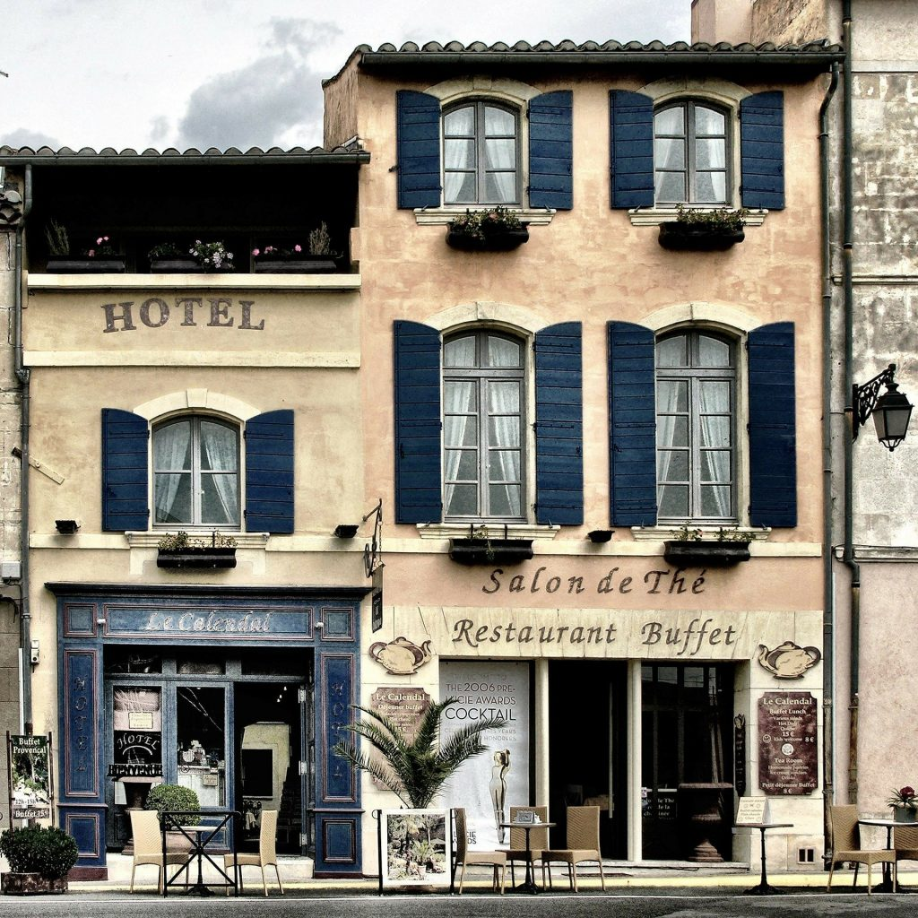A quaint three-story hotel with arched windows and black shutters. A Salon de The and Restaurant Buffet are on the ground floor with doors open to a sidewalk with several small tables.