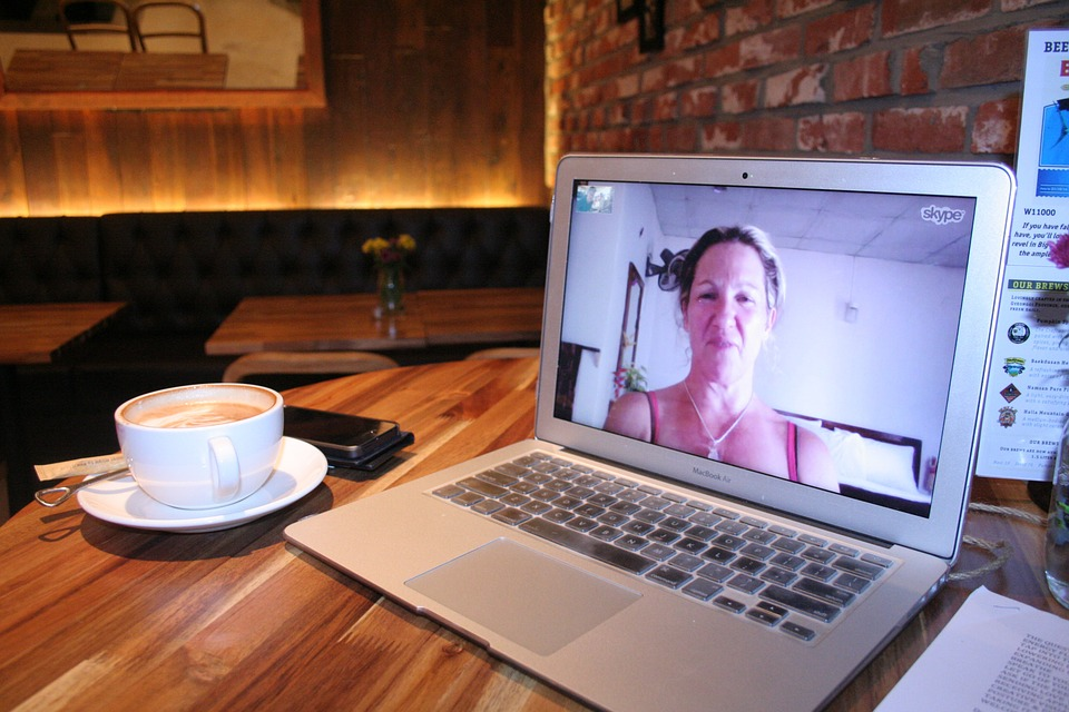 A laptop sitting on a table next to a cup of coffee. A Skype video chat with a blond woman is fullscreen.