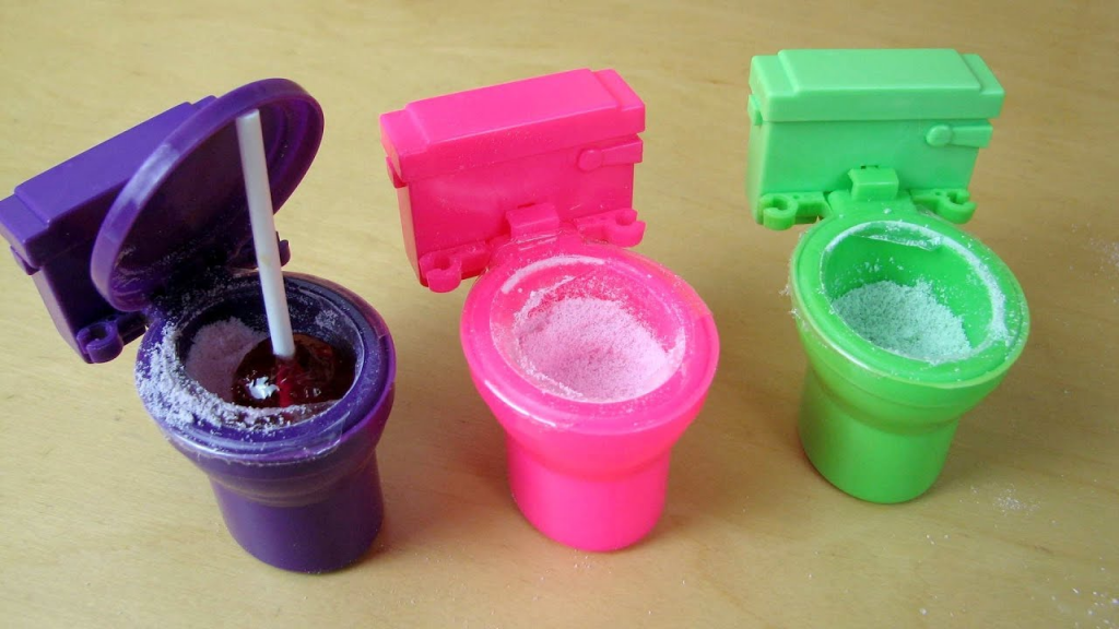 3 small plastic toilets (purple, pink, green) with sour candy powder in the bowls and a lollipop sticking out of the purple on on the far left.