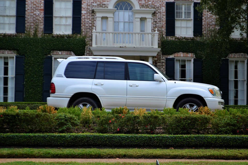 A white SUV parked in front of a larger brick house. Some shrubbery in the foreground.