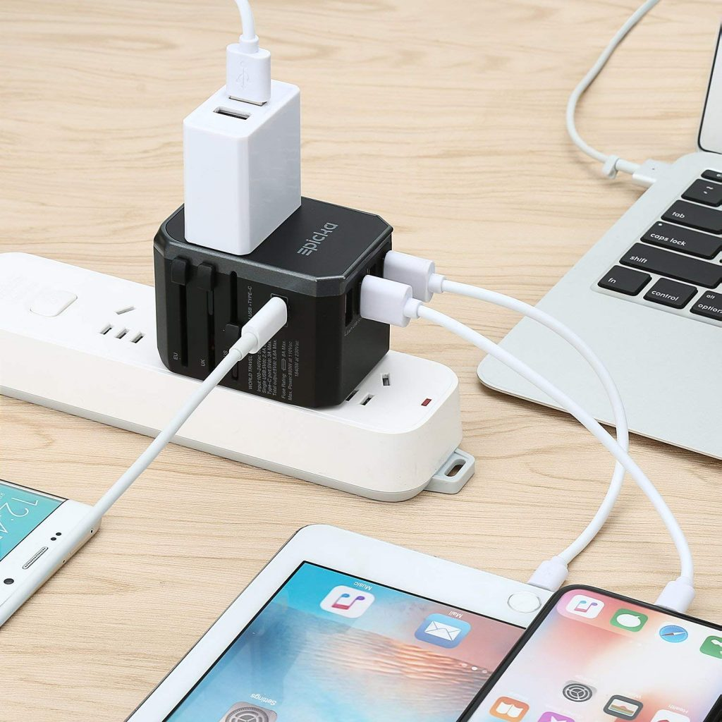 A universal travel adapter plugged into a power strip charging a laptop, tablet, and two phones.