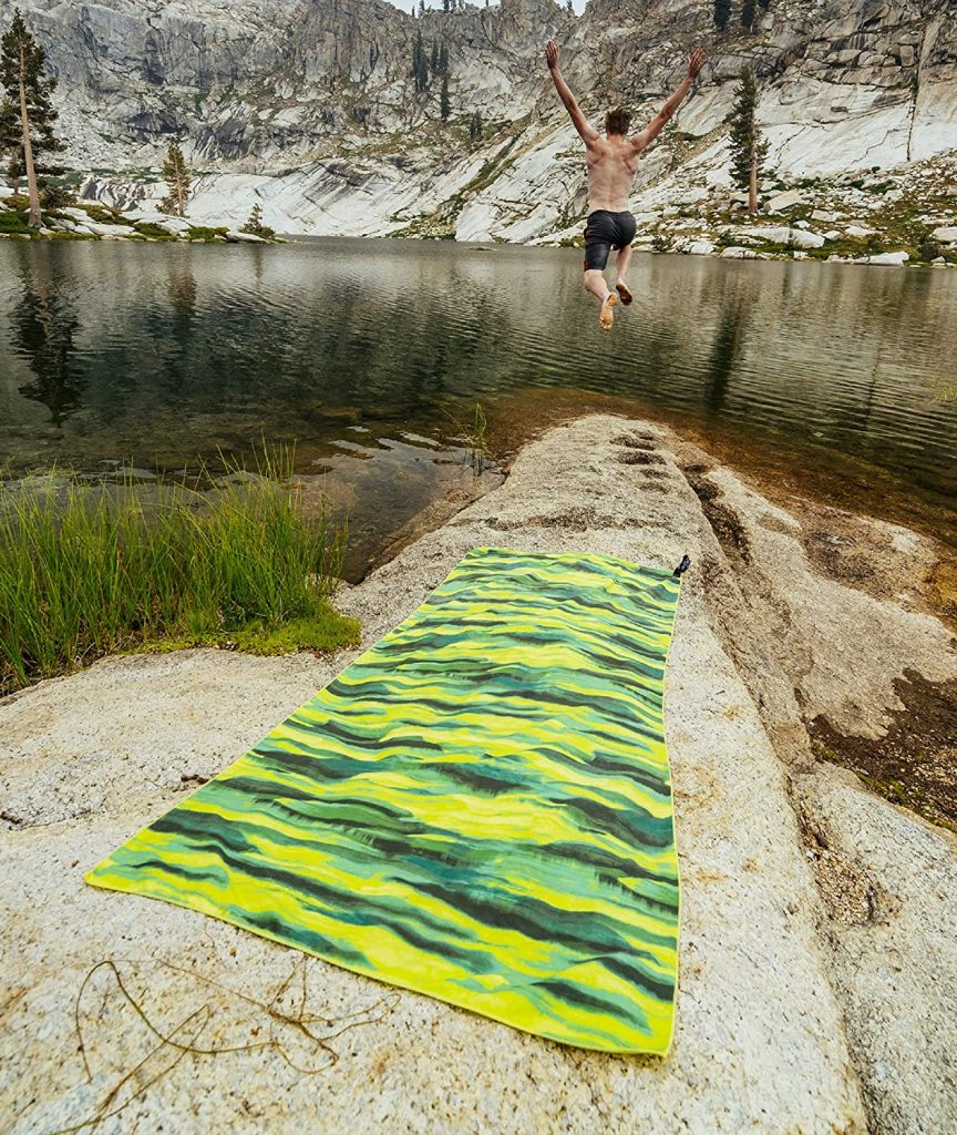 A green microfiber travel towel on the rocky shore of a lake with a man jumping into the lake in the distance.