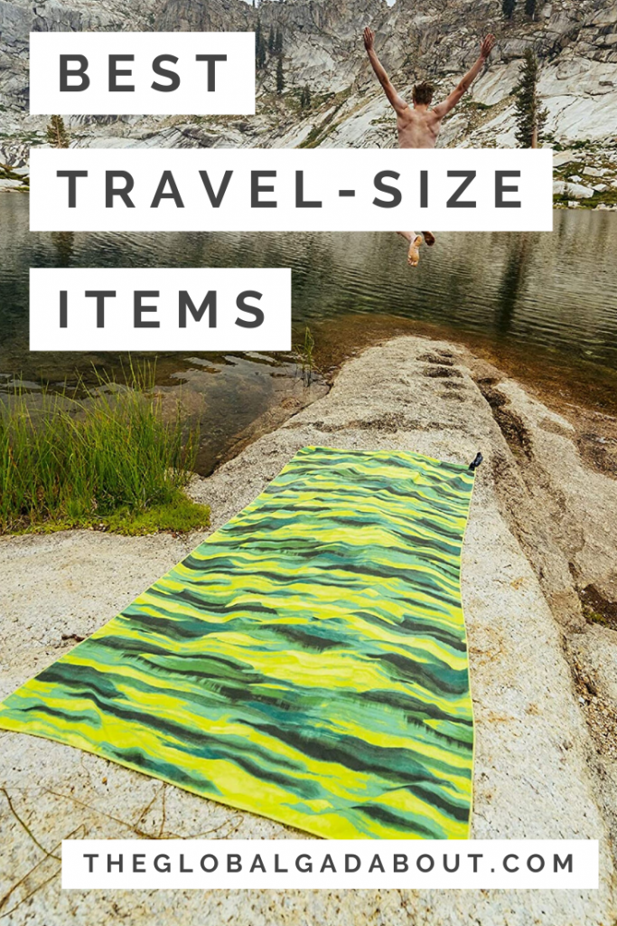 "A green microfiber travel towel on the rocky shore of a lake with a man jumping into the lake in the distance. White rectangles overlaying the image with black words reading, ""Best Travel-Size Items"" and ""TheGlobalGadabout.com""."