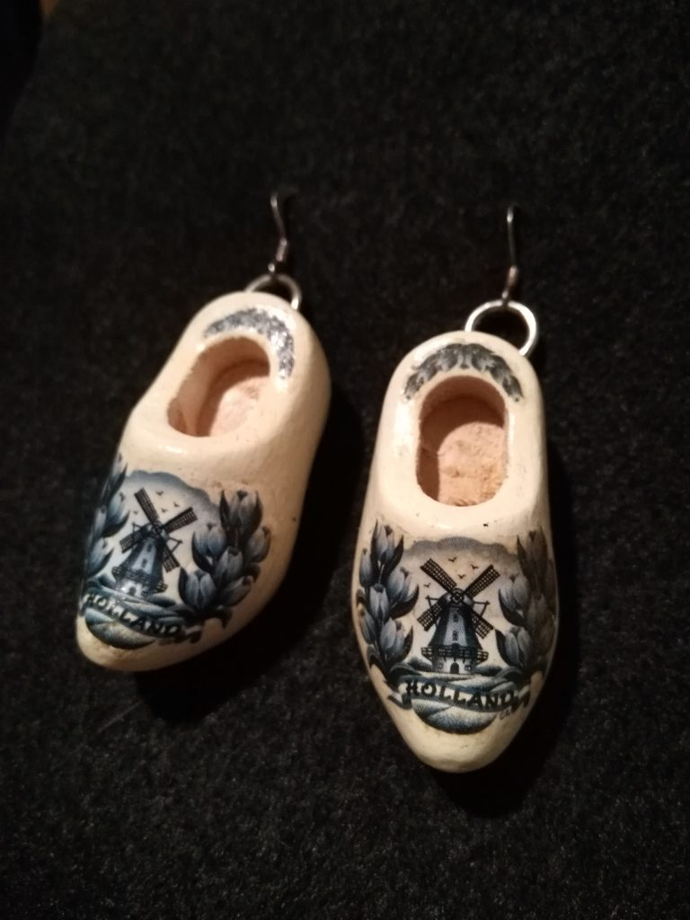 "A pair of white, wooden clog earrings with blue windmills and the word ""Holland"" on the toes."