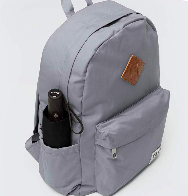 A gray backpack with a black umbrella in the side pocket.