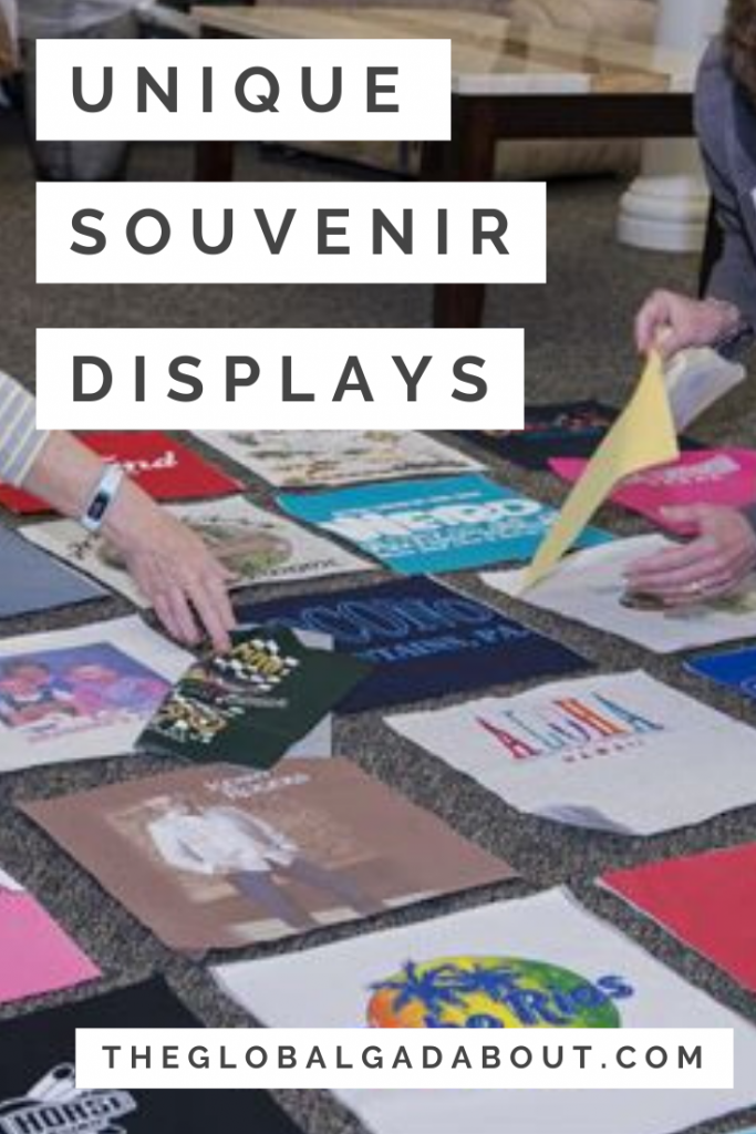 "Hands arranging a bunch of squares cut from the front of t-shirts in a grid on the floor. White blocks on top have the words ""Unique Souvenir Displays"" and ""TheGlobalGadabout.com"" in black."