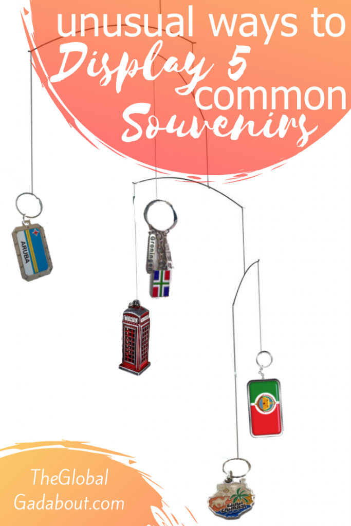 "A hanging key chain mobile on a white background. In the top right corner a red circle has the words ""Unusual Ways to Display 5 Common Souvenirs"" in white. In the bottom left corner, a similar circle as the words ""TheGlobalGadabout.com""."