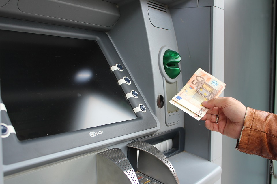 ATM screen with a hand holding two 50 euro notes.