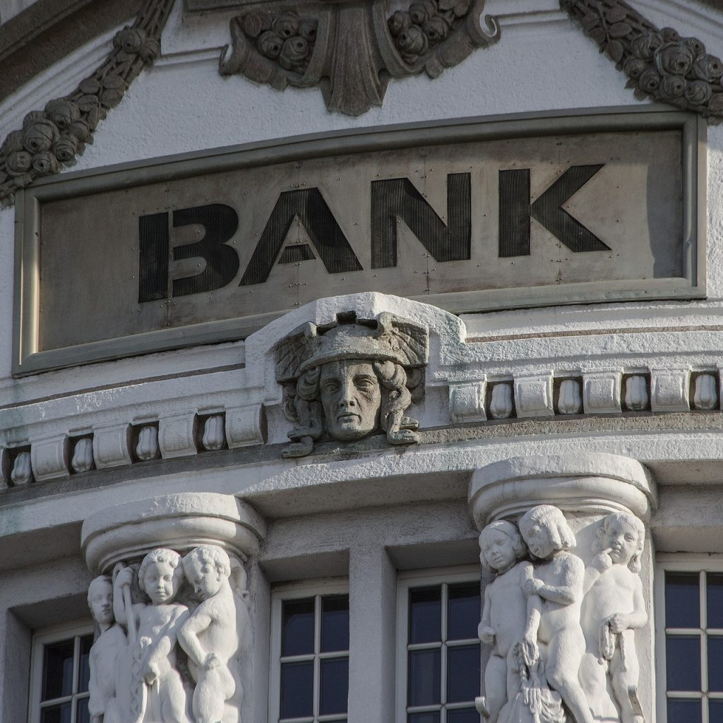 "Close up of part of a building with the tops of two pillars, several carved figures & faces and the word ""Bank""."