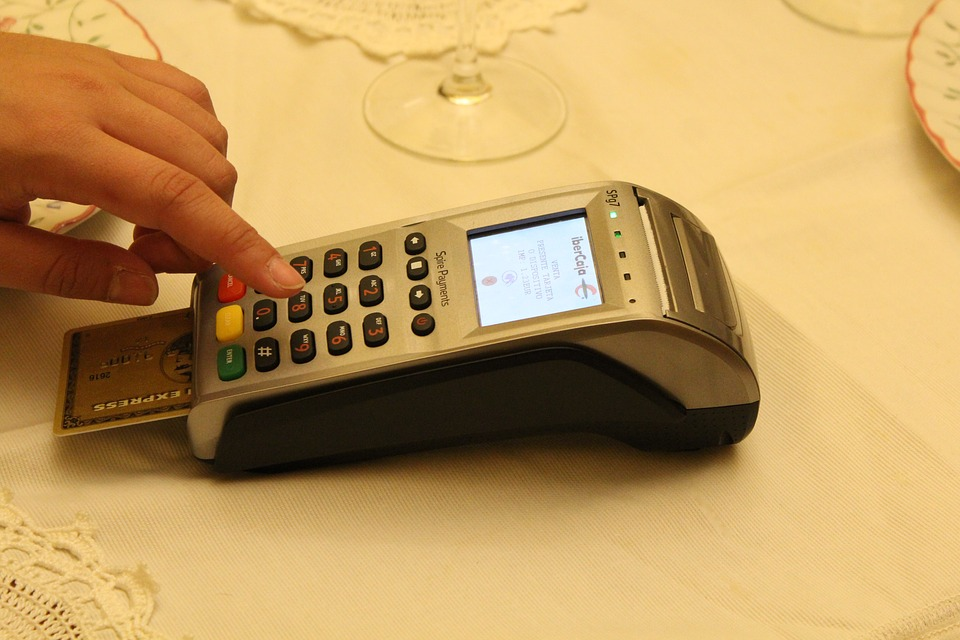 Credit card payment terminal sitting on a restaurant table with a credit card in the chip reader. A hard is pressing a button.