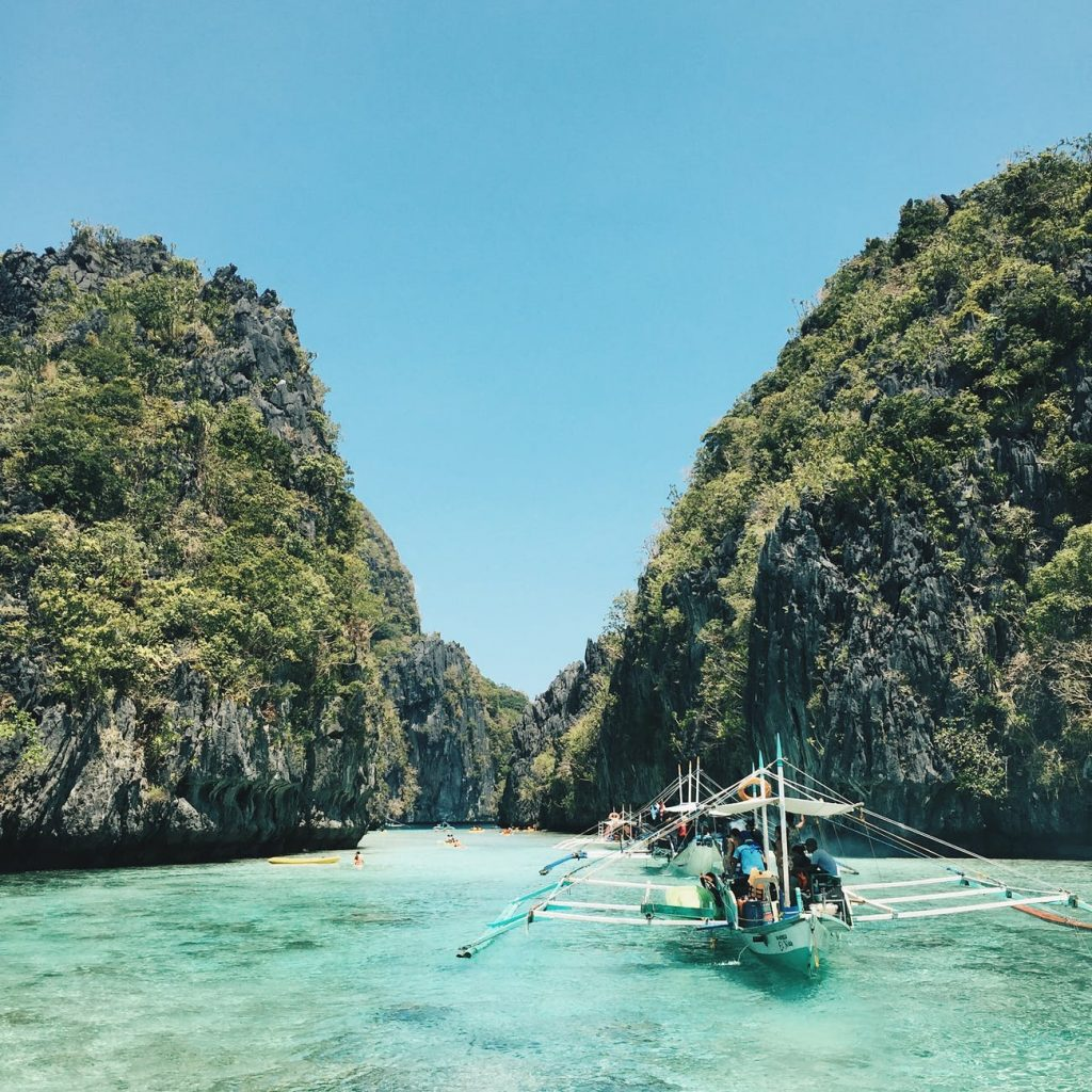 Tropical water with several boats surrounded by high cliffs in the Philippines.