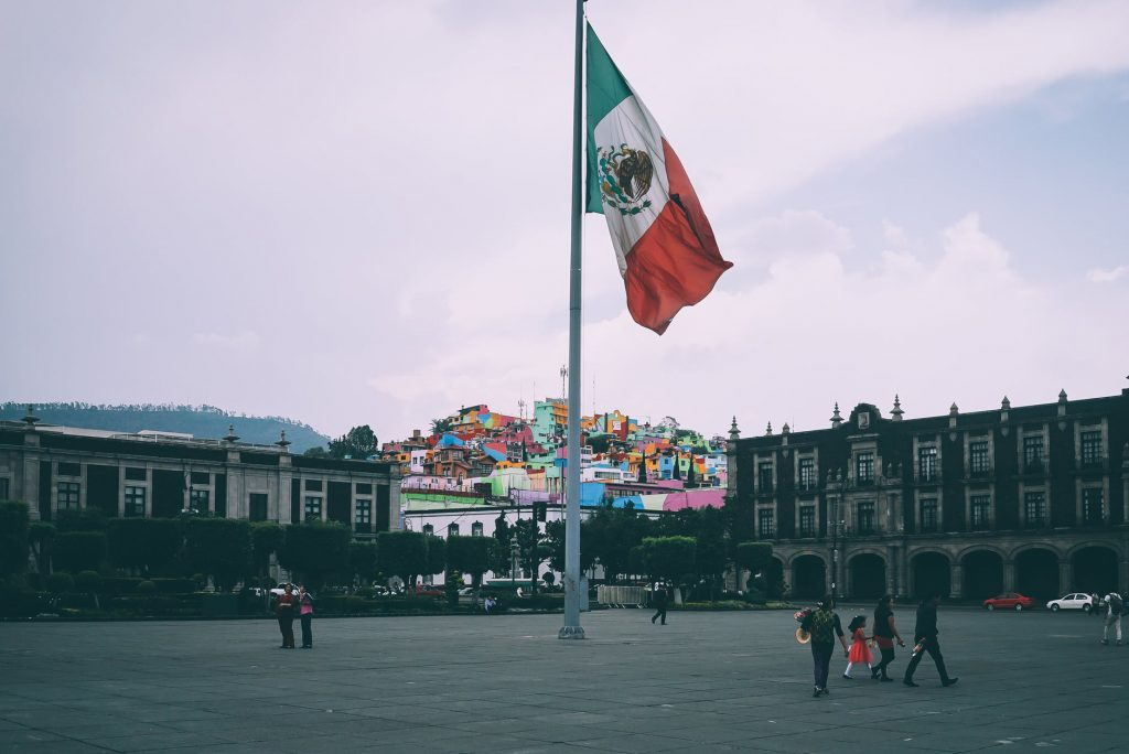 Mexican city square with a large flag in the middle.