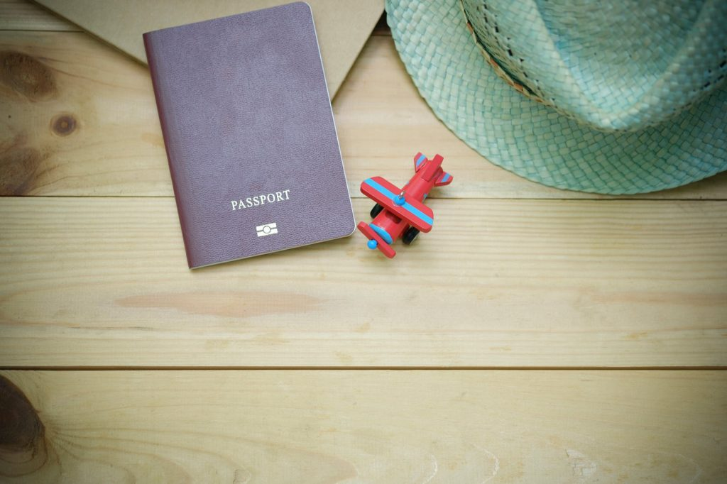 Wooden table with a passport, sun hat, and toy airplane.