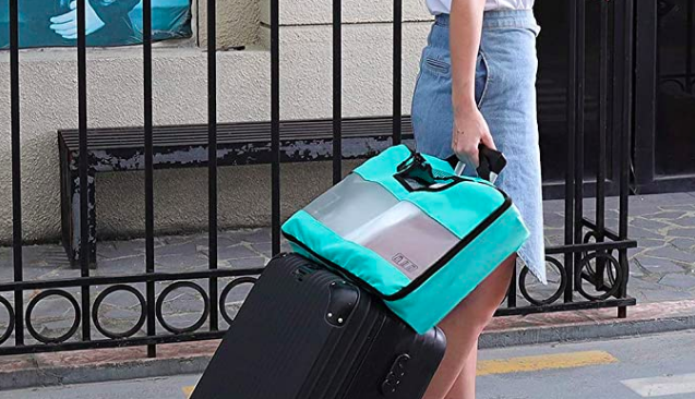 A woman walking down a street with a rolling suitcase and a packing cube stacked top, leaning against the suitcase handle.
