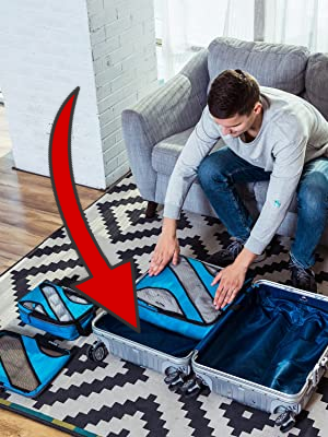 Man sitting on a couch packing a suitcase with packing cubes on the floor. A large red arrow points to unused space in the suitcase where a packing cube won't fit.