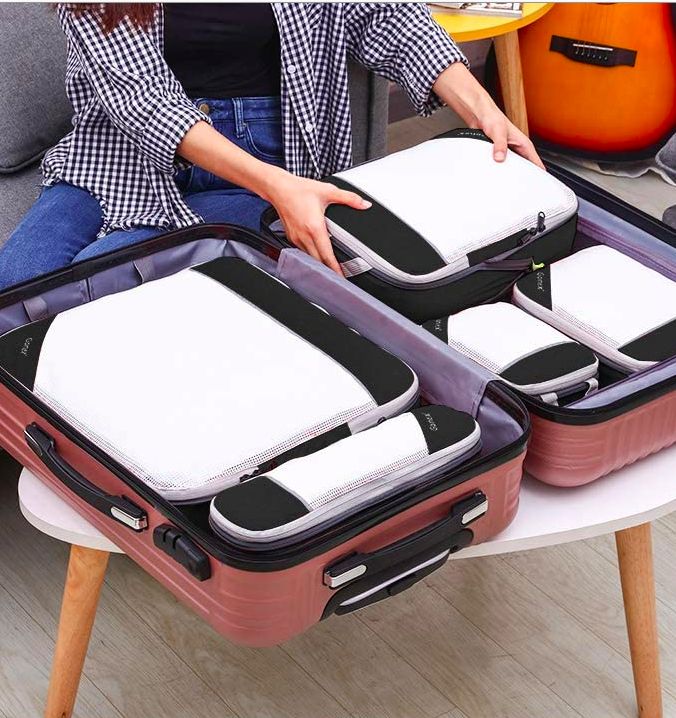 An open suitcase full of packing cubes. Hands are placing the last packing cube neatly in the suitcase.