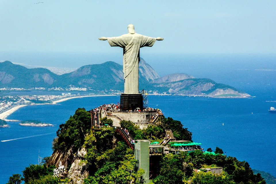 Christ the Redeemer statue from behind with the beach and mountains of Rio de Janeiro.