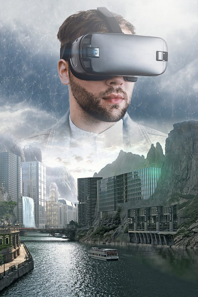 A river with a ferry and skyscrapers set into the cliffs on both sides of the river, a bridge and waterfall in the distance. A man's face wearing a virtual reality headset is floating in the sky, which has looks slightly digital.