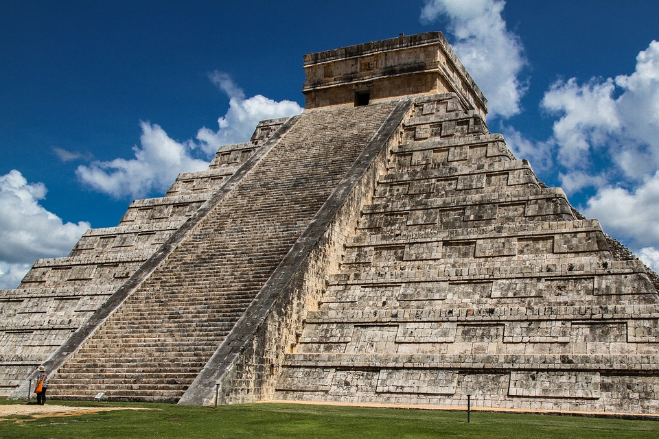 El Castillo step-pyramid at Chichen Itza in Mexico with a blue sky behind.