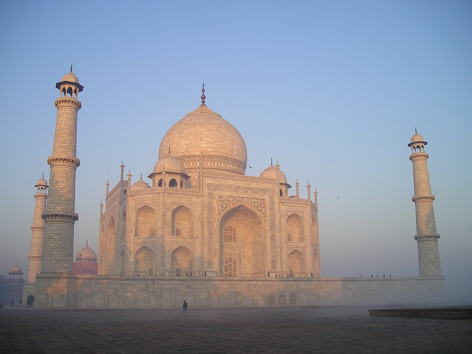 The Taj Mahal at dusk or dawn with a clear blue sky behind.