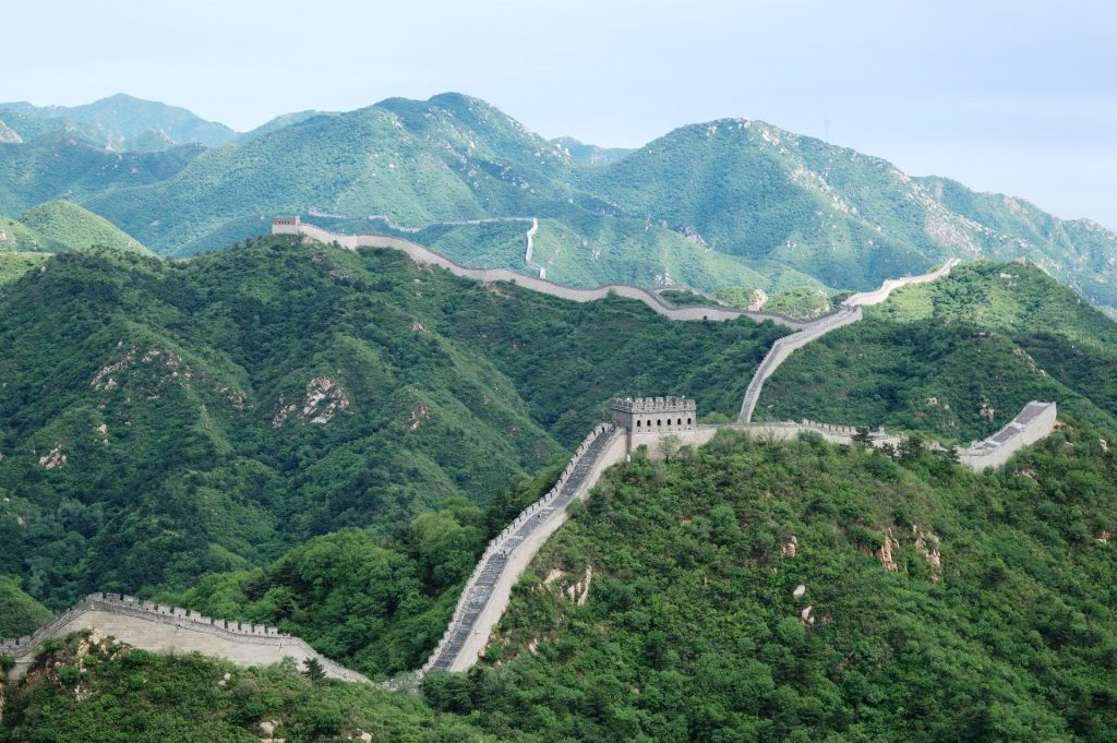 The Great Wall of China zig-zagging across green hills.