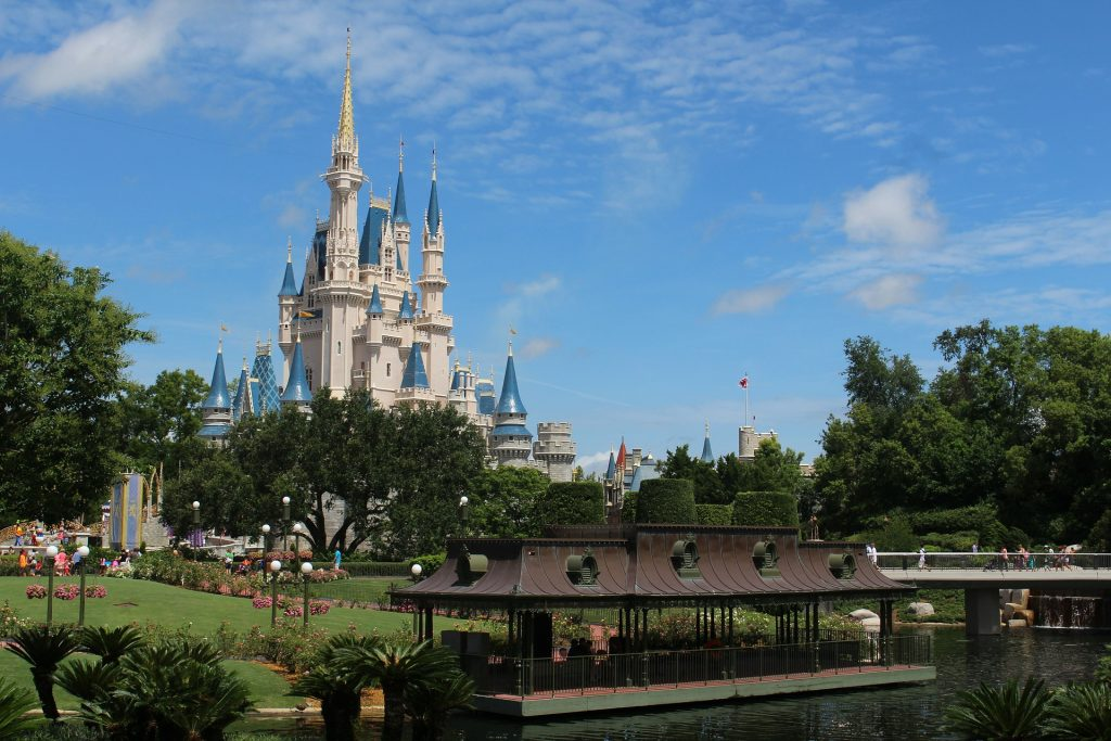 Cinderella's castle at Disney World from a distance with a green area and pond in the foreground.
