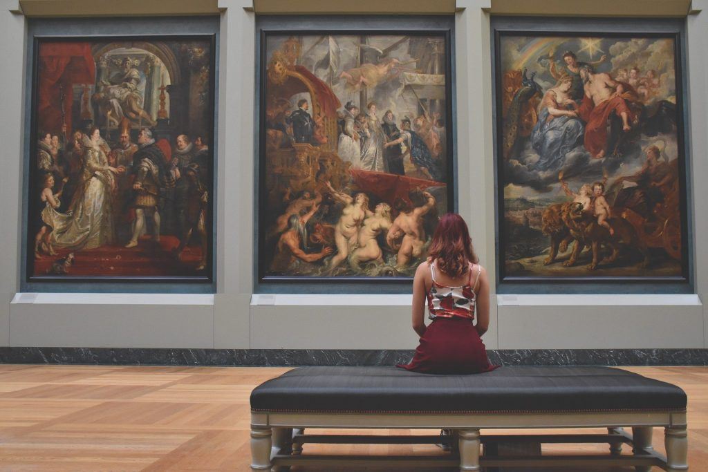 Three large paintings in the Louvre Museum with a woman sitting with her back to camera looking at the paintings.