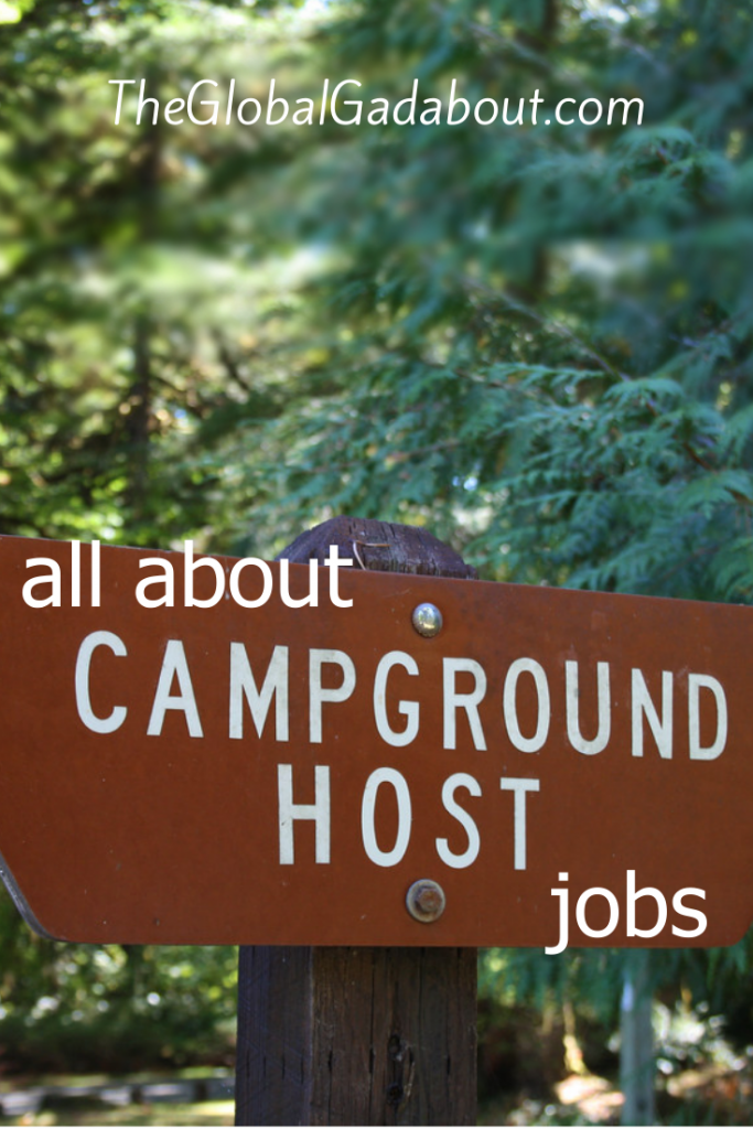 "A wooden sign in the woods and the words ""all about Campground Host jobs"" and ""TheGlobalGadabout.com"" in white."