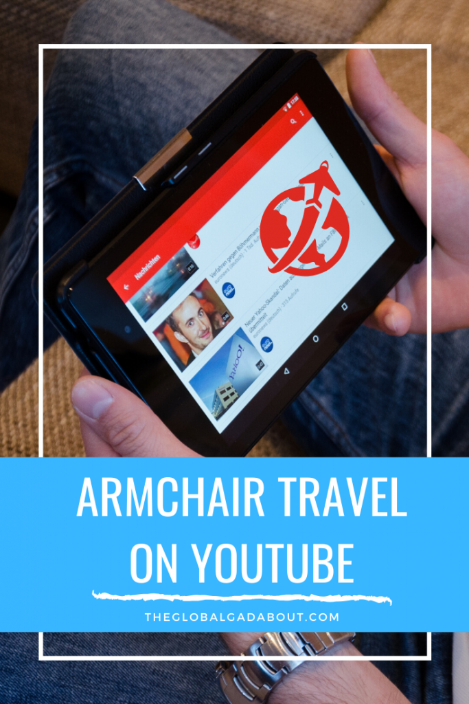 "Seated person holding a tablet with YouTube and a travel icon on the screen. Only the person's hands and legs are showing. A blue box at the bottom has the words ""Armchair Travel on YouTube"" and ""TheGlobalGadabout.com"" in white."
