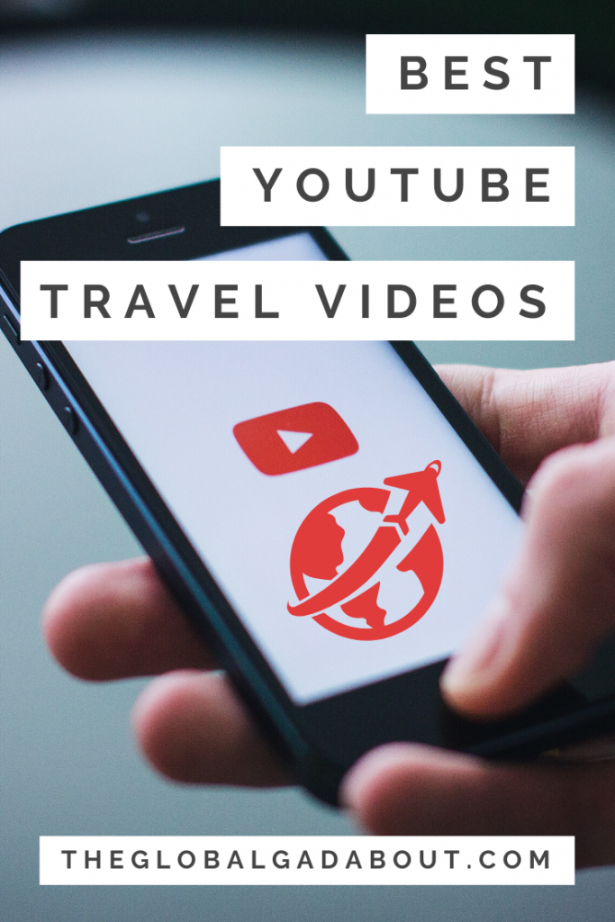 "A hand holding a phone with a YouTube play symbol and a globe with an airplane symbol on the screen. The words ""Best YouTube Travel Videos"" and ""TheGlobalGadabout.com"" are superimposed with white boxes around them."