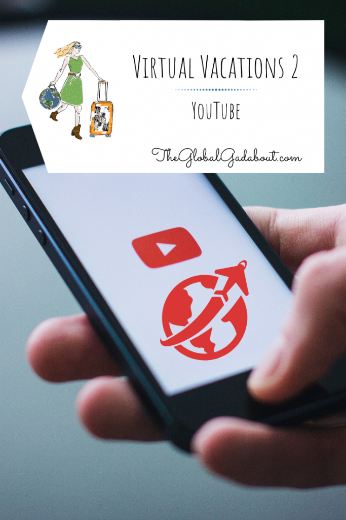"A hand holding a phone with a YouTube ""play"" symbol and an airplane circling the world graphic on the screen. A white luggage tag shaped box is superimposed at the top with The Global Gadabout symbol and the words ""Virtual Vacations 2: YouTube"" and ""TheGlobalGadabout.com""."