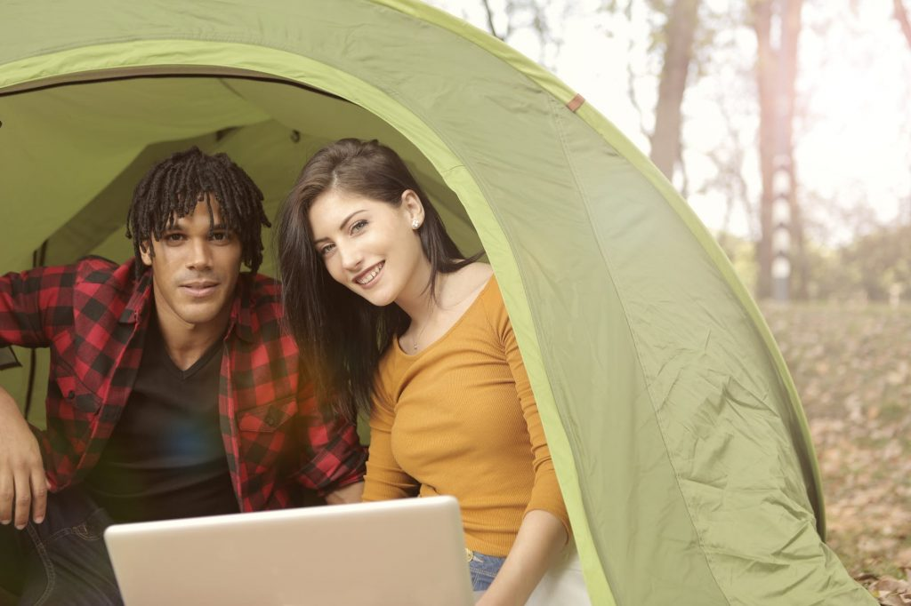 A close up of the opening of a tent. A young man and woman look out the open tent door with a laptop in front of them.