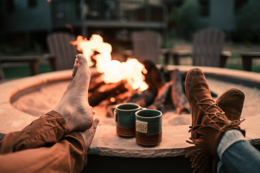 A campfire in a fire pit with chairs in the background. Two sets of crossed feet and two mugs are in the foreground.