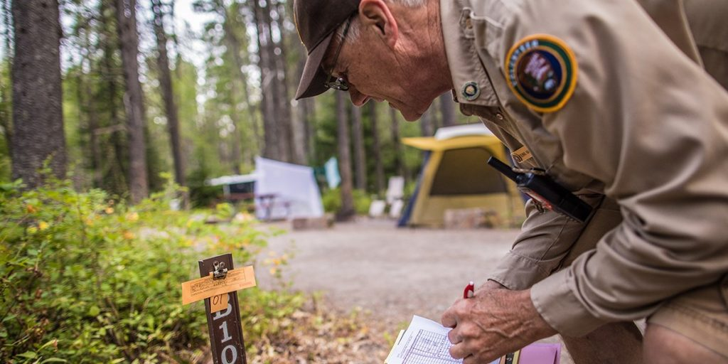An older man in uniform leans over at a campsite and marks something on a paper in his hand.
