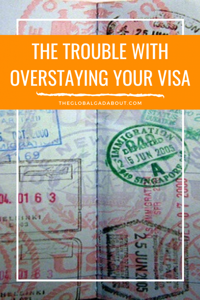 "A visa page from a passport with lots of stamps. An orange box covers the top with the words, ""The Trouble With Overstaying Your Visa"" and ""TheGlobalGadabout.com"" in white."